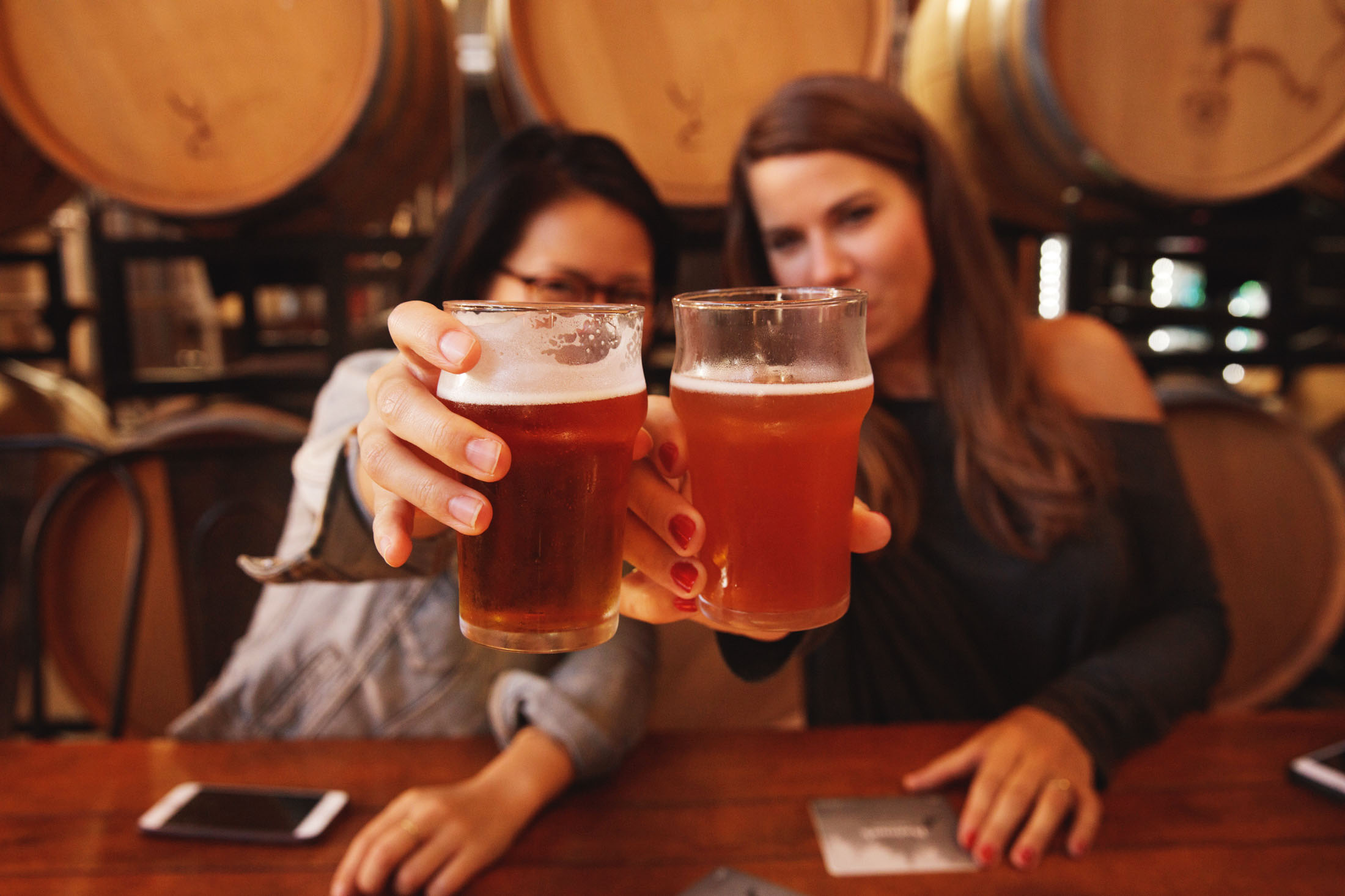 Two woman toasting with beers in craft brewery in Vancouver