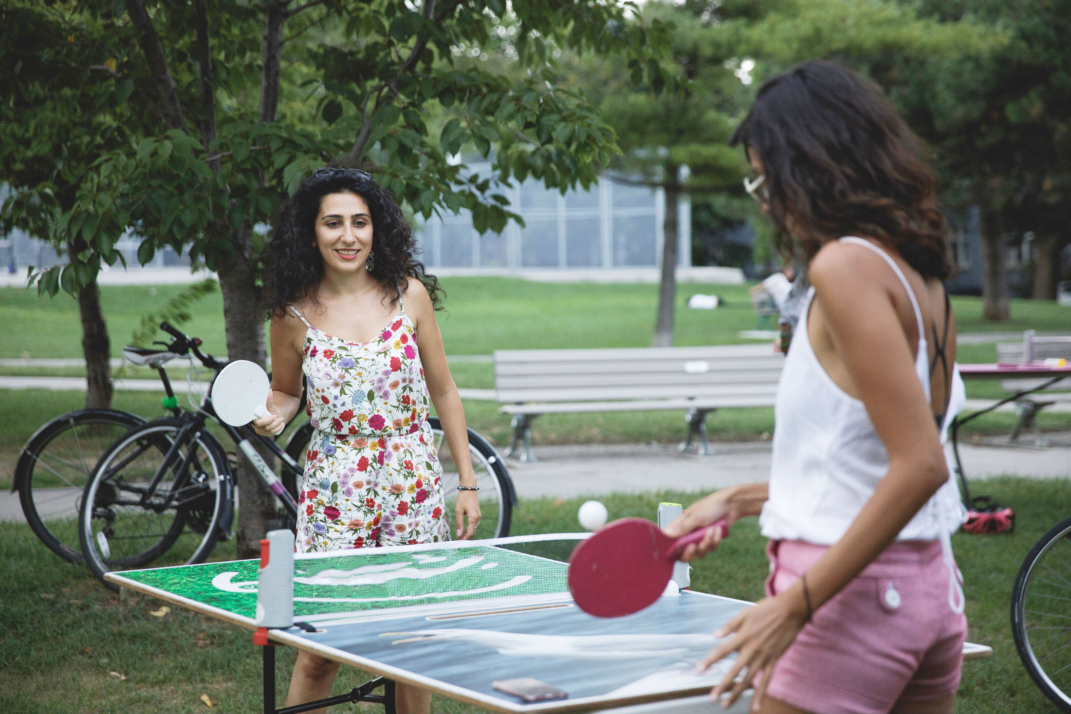 Two young women playing outdoor table tennis in Toronto
